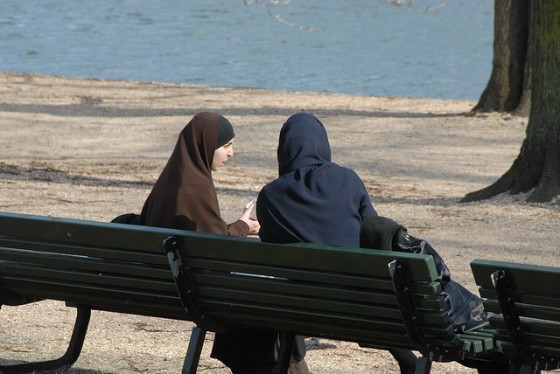 Two women in hijab sit on a bench, eating.