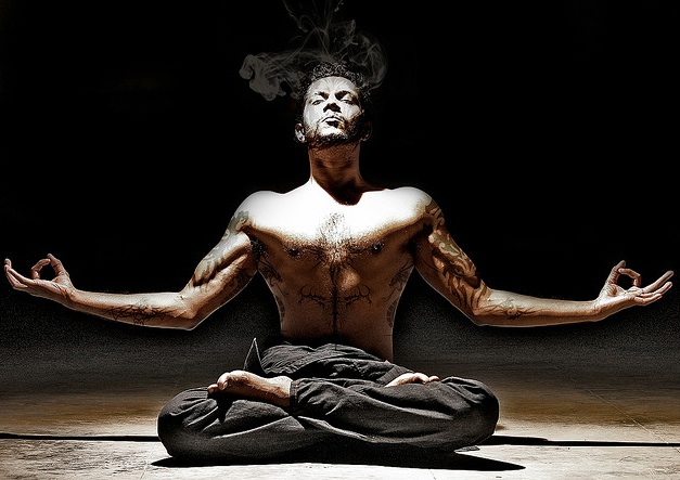 man doing yoga and meditating, shirtless, black pants, smoke