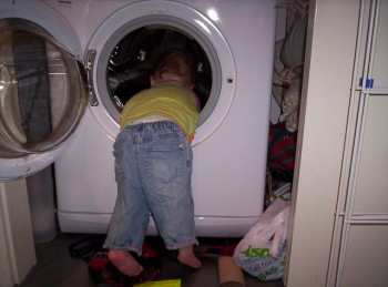 toddler peeking into the washing machine