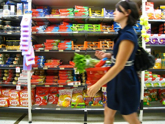 young woman purchasing greens in grocery, candy in background