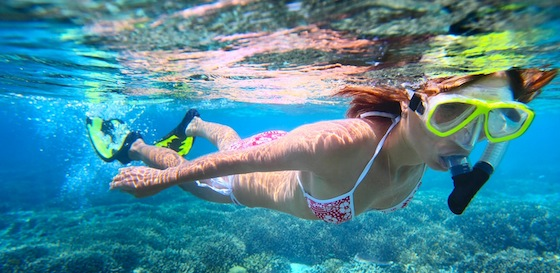 woman snorkels over coral reef