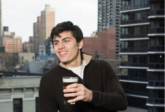 man drinking beer balcony