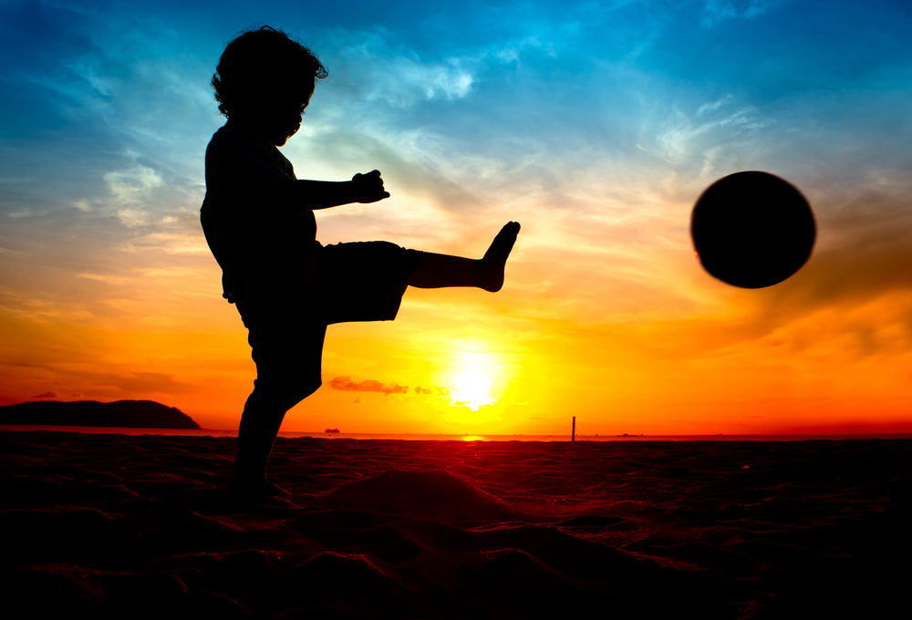 child_with_soccer_ball_at_sunset