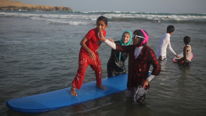 Mona And Easkey help young girl to surf.