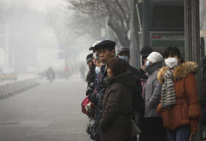 Commuters, some wearing masks to protect themselves from pollutants, wait at a bus stand on a heavily polluted day in Beijing, Monday, Nov. 30, 2015. Beijing on Sunday, Nov. 29 issued its highest smog alert of the year following air pollution in capital city reached hazardous levels as smog engulfed large parts of the country despite efforts to clean up the foul air. (AP Photo/Andy Wong)