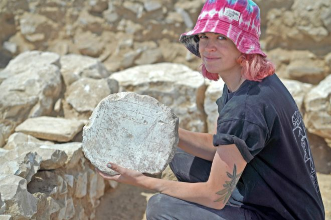 ancient game found in Israel, held by a woman archeologist wearing a pink hate
