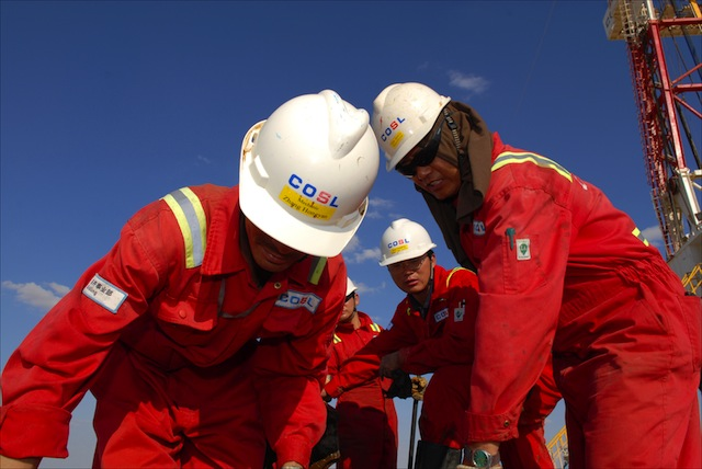 Chinese oil workers repair a valve at a rig near Faregh, Libya, deep in the Sahara Desert. The rig is operated by China Oilfield Services Ltd. (COSL).