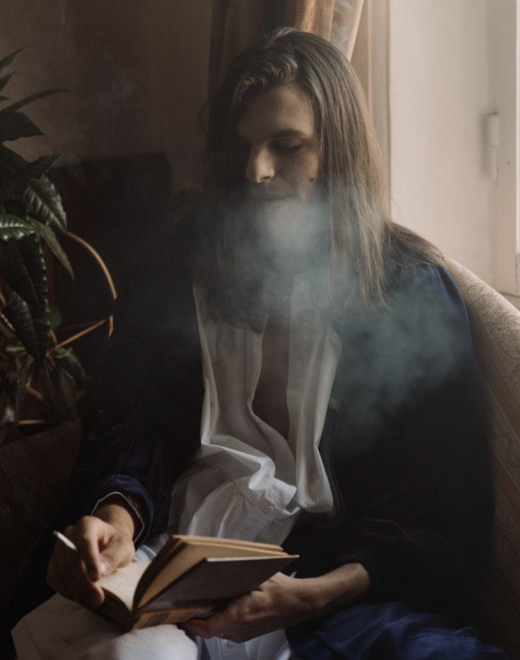 hipster reads book while smoking a joint