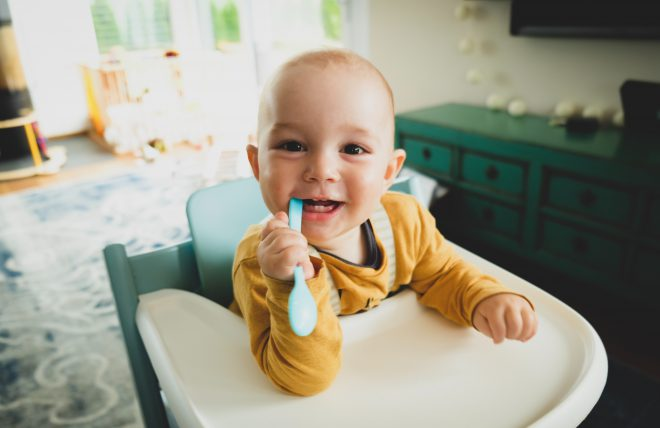 baby sucking on toothbrush, yellow shirt in highchair in green kitchen happy
