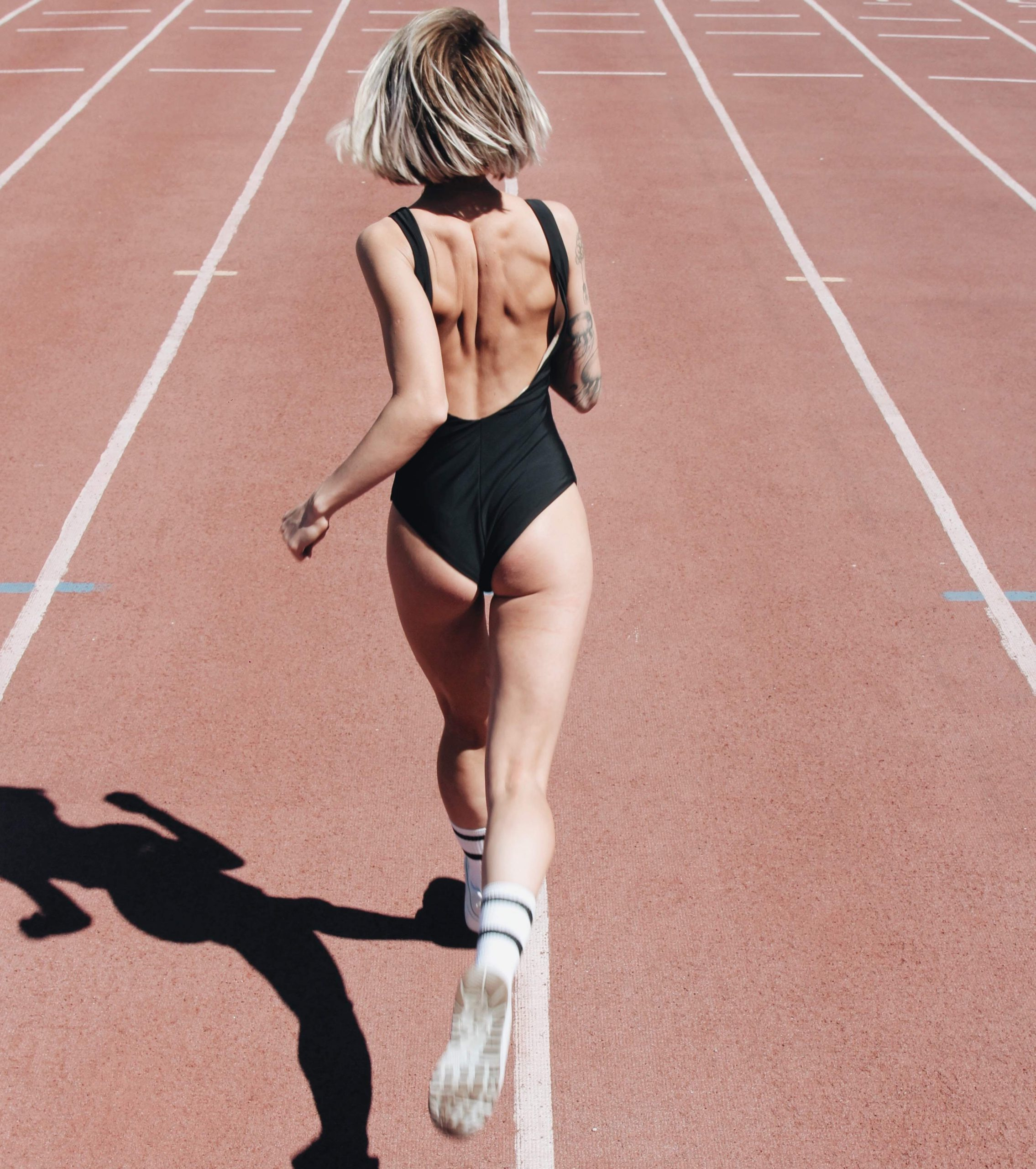 woman running in black body suit on a track