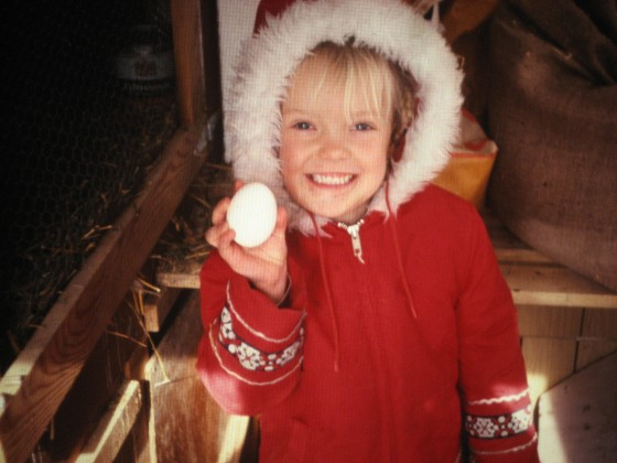 karin kloosterman, wearing parka holding an egg, little blond girl 5 years old