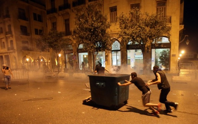 "Lebanese demonstraters take shelter behind a rubbish container during clashes with security forces following a demonstration, organised by the ""You Stink"" campaign, against the ongoing trash crisis in the capital Beirut on August 22, 2015. Thousands of protesters, including children, gathered to protest the Lebanese government's inability to find a lasting solution to the country's worsening waste problem. AFP PHOTO / STR"