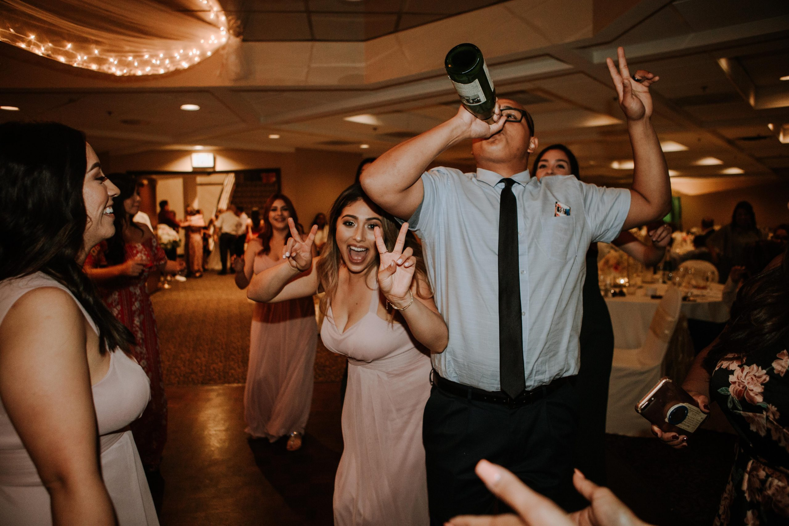 man drinking at a wedding