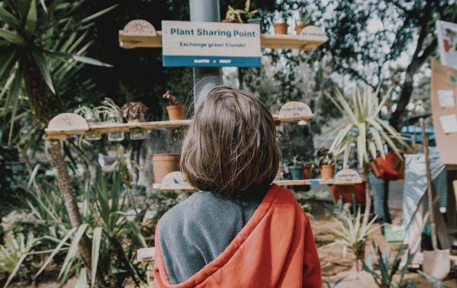 little girl looks into plant sharing in the park