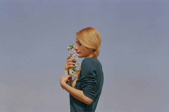 blond woman in green sweater smelling white flowers, sky background