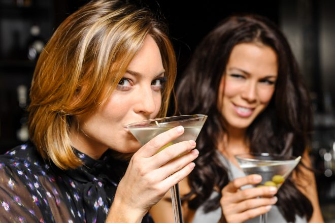 attractive women, a blond and a brunette drinking martinis with olives.