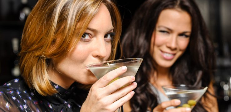attractive women drinking martinis, smiling