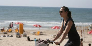 woman cycling Tel Aviv beach