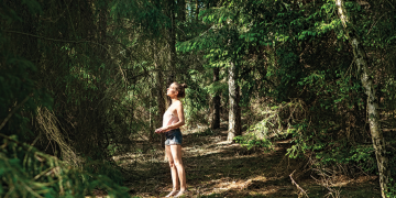 forest bathing, woman hipster contemplating nature in dark green forest