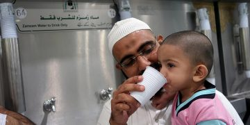 father feeding zam zam water to his boy